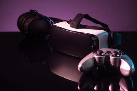 Joystick, VR headset and headphones on dark violet background Stock fotó