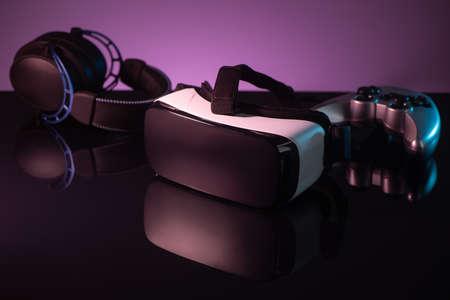 VR headset, joystick and headphones on dark violet background