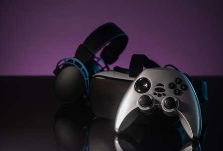 Joystick, headphones and VR headset on dark violet background