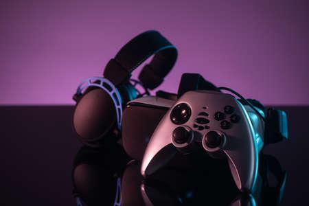 Set of joystick, VR helmet and headphones on dark violet background