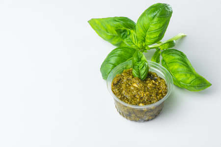 Small cup of pesto sauce with a basil leaves on white background