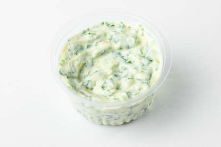A cup of tartar sauce on white background