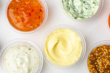 Top view on various sauces in small cups on white background Stock fotó