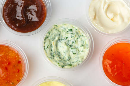 Top view on assortment of different sauces in small cups on white background