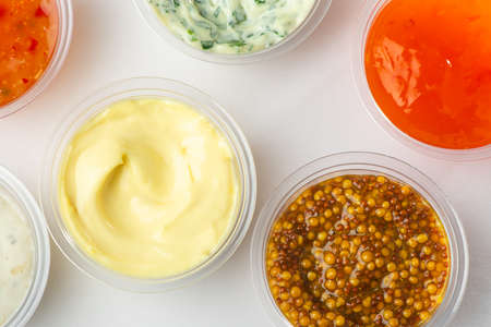 Top view on cups of various sauces and condiments on white background