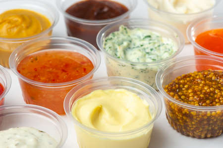 Variety of different sauces and condiments in small cups on white table