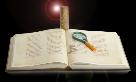 book with a magnifying glass and a candle on a black . photo