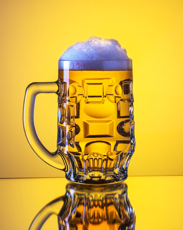 Mug fresh beer with cap of foam isolated over yellow background. Stock Photo - 25897804