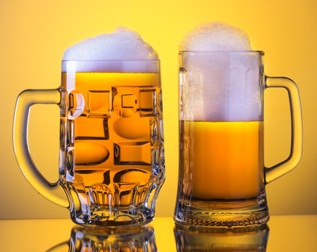 Two Mugs of fresh beer with cap of foam, isolated on yellow background. Stock Photo - 25897814