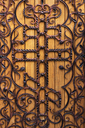 forged wooden door with a cross in the church. photo
