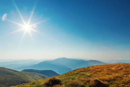 sunshine background: bright sun in mountains.