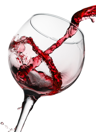 red wine pouring in glass isolated on white background. Standard-Bild