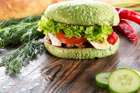 vegetarian hamburger: burger with green bun on wooden background. Stock Photo