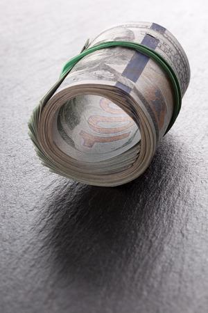 money roll: money roll dollars on a slate table.