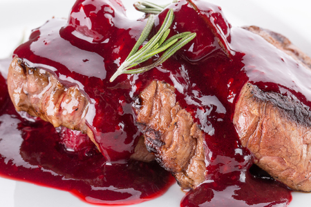 close up of sliced meat in cranberry sauce. Stock Photo