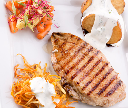 korean salad: meat steak with baked potatoes with tartar sauce and korean carrots. Stock Photo