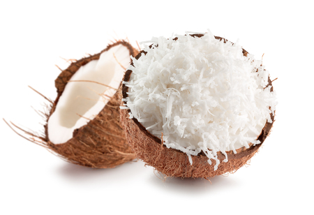 two halves of coconut with coconuts flakes isolated on a white background.