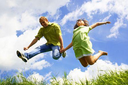 pareja saludable: Salto de personas de la felicidad en el cielo azul y fondo de hierba verde  Foto de archivo