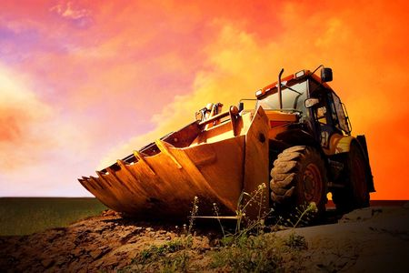 gold shovel: Yellow tractor on golden surise sky