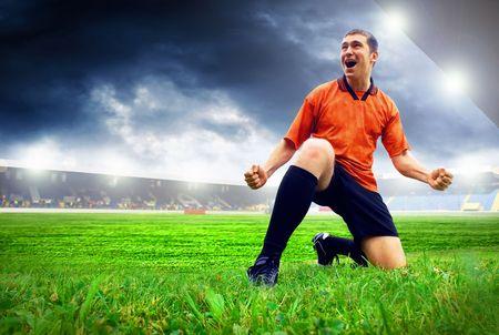 futbolistas: Jugador de fútbol americano de felicidad después de gol en el campo del estadio con cielo azul