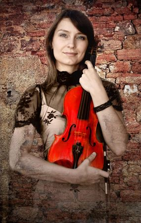 Beautiful female violinist with violin on the grunge background photo