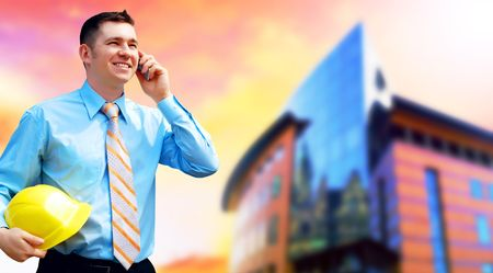 Young architect wearing a protective helmet standing on the building background Stock Photo - 7739779