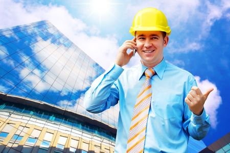 happyness: Young architect wearing a protective helmet standing on the building background Stock Photo