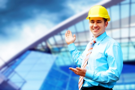 foreman: Young architect wearing a protective helmet standing on the building background Stock Photo