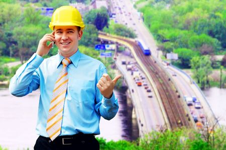 Young architect wearing a protective helmet standing on the building background Stock Photo - 7739751