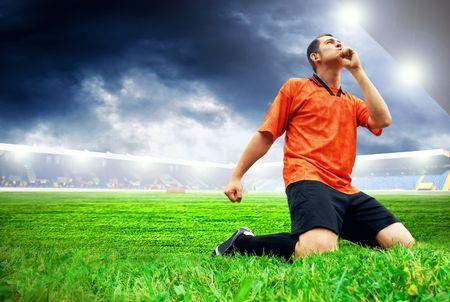 Jugador de fútbol americano de felicidad después de gol en el campo del estadio con cielo azul  Foto de archivo