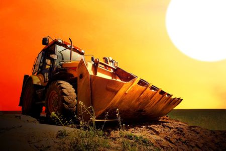 Yellow tractor on golden surise sky photo