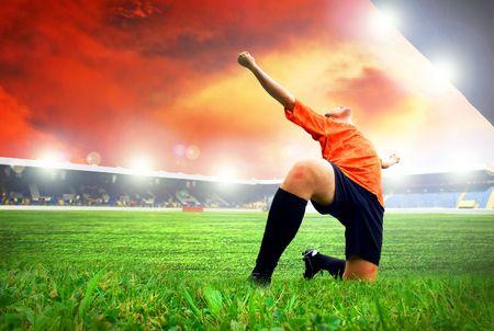 Jugador de fútbol americano de felicidad después de gol en el campo del estadio con cielo azul
