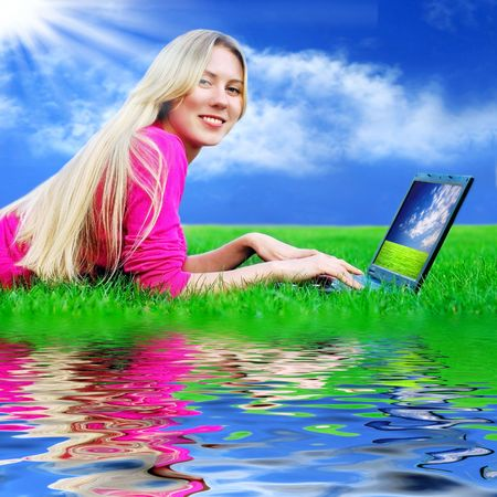 Beautiful girl with laptop on the blue sky and green grass background  Stock Photo