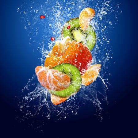 jugo de frutas: Gotas de agua alrededor de frutas sobre fondo azul  Foto de archivo