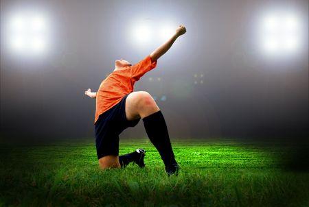 futbolistas: Jugador de fútbol americano de felicidad después de gol en el campo del estadio con la luz  Foto de archivo