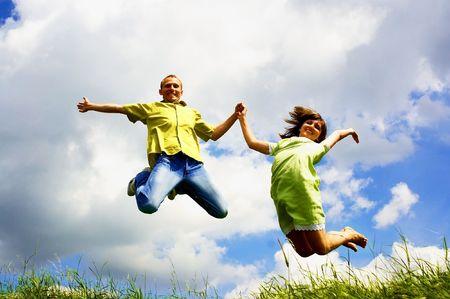 青い空と緑の草の背景に幸福の人々 のジャンプ