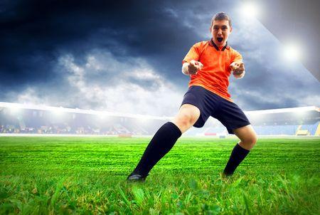 Joueur de football de bonheur après le but sur le terrain du stade avec ciel bleu  Banque d'images - 7851254