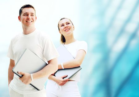 Pair of two happy young people or student with laptops on the business background photo
