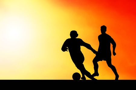 Silhouettes of footballers on the sunset sky photo