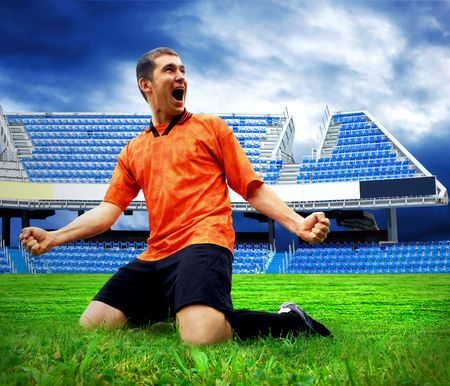Happiness football player after goal on the field of stadium under sky photo