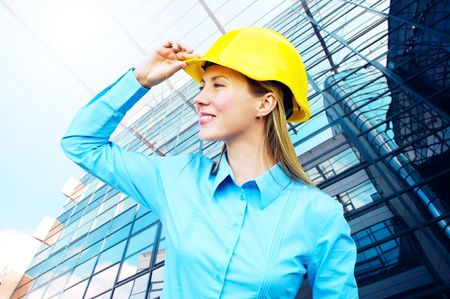 Young architect-woman wearing a protective helmet standing on the building background photo