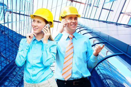Young architects wearing a protective helmet standing on the building background Stock Photo - 7851485