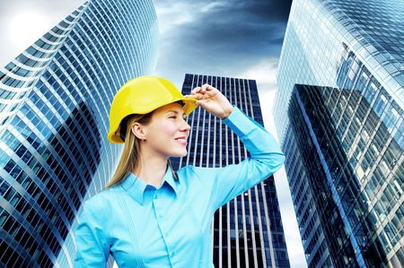 female engineer: Young architect-woman wearing a protective helmet standing on the building background