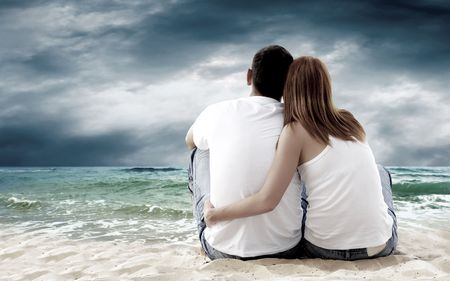 male and female: Sea view of a couple sitting on beach. Stock Photo