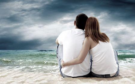 modelos masculinos: Vista al mar de una pareja sentada en la playa.