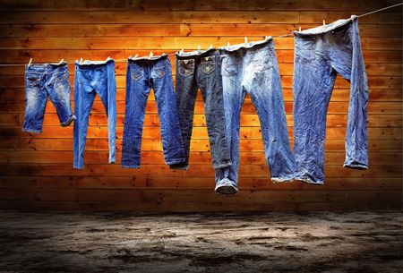 Jeans on a clothesline to dry on the grunge background photo