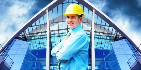 Young architect wearing a protective helmet standing on the building background Stock Photo - 7927984