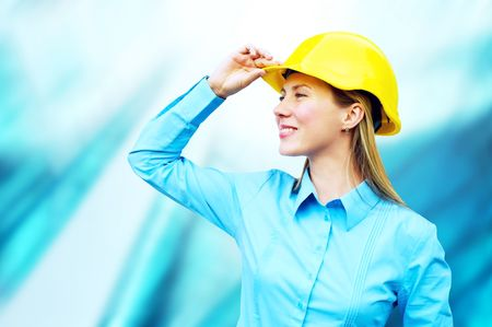 Young architect-woman wearing a protective helmet standing on the building background Stock Photo - 7928111