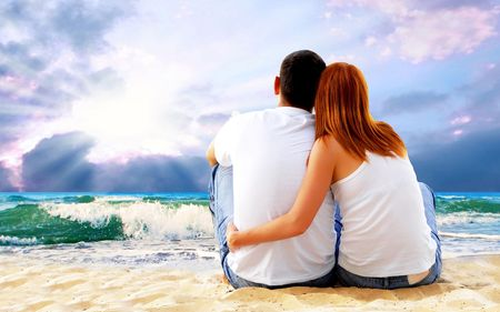 Sea view of a couple sitting on beach. Banque d'images