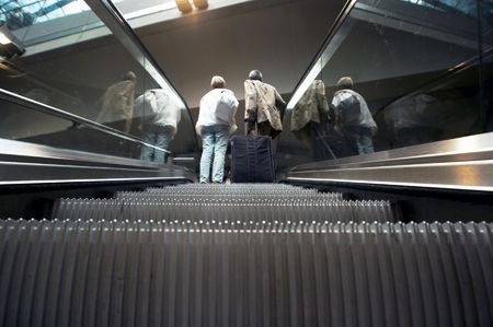 Two passangers with bag on railway station escalator photo